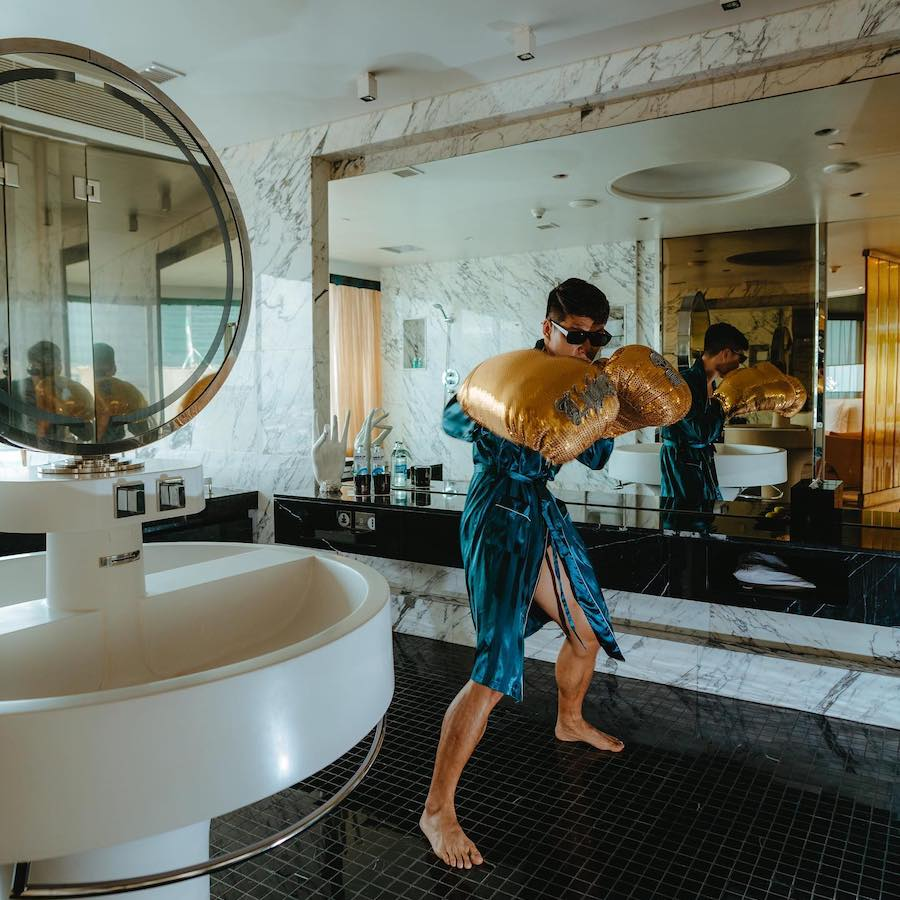 Thai guy wearing huge boxing gloves in wow extreme suite at W hotel Bangkok