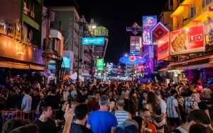 Bangkok famous party street Khoasan road at night with neon signs and people partying and drinking