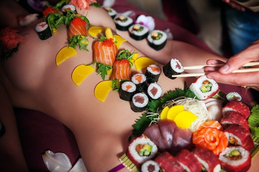 body of a naked girl covered with sushi