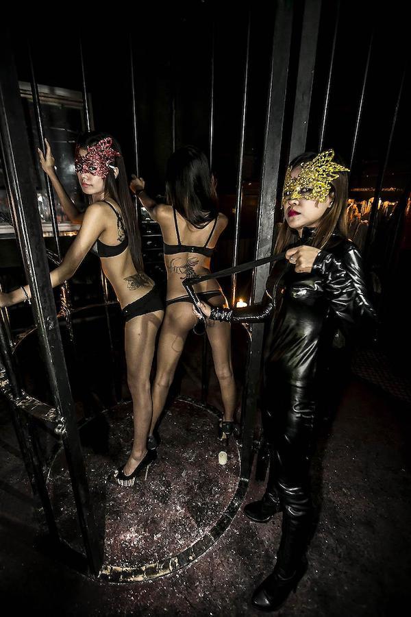 Thai girls with masquerade mask and whip at bdsm club in Bangkok
